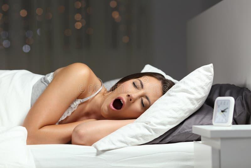 Slaperige vrouw geeuw klaar aan slaap op een bed stock afbeelding