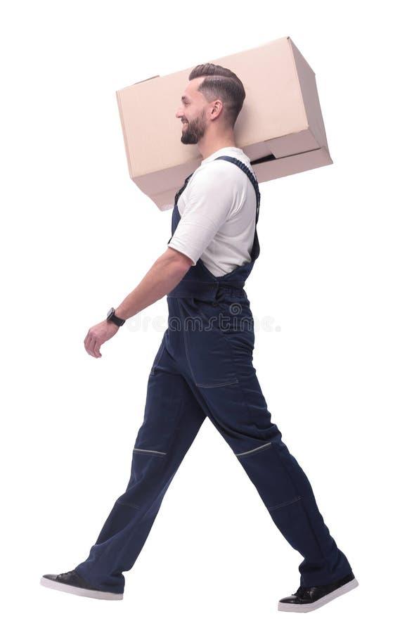 Slapp fokus en man i overaller bär en stor kartong arkivfoto