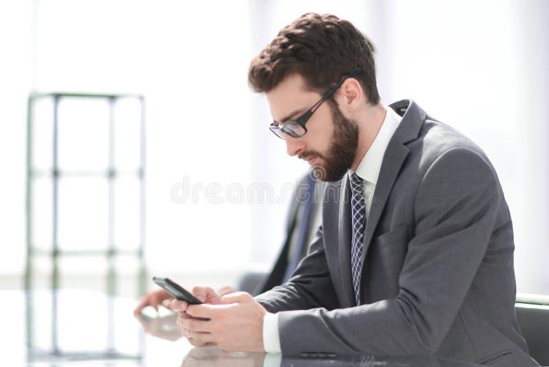 Slapp fokus en stilig affärsman använder en smartphone arkivbilder