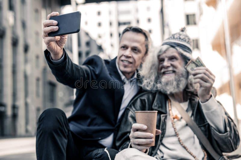 Slarvig långhårig arbetslös man som sitter på kall jordning arkivfoto