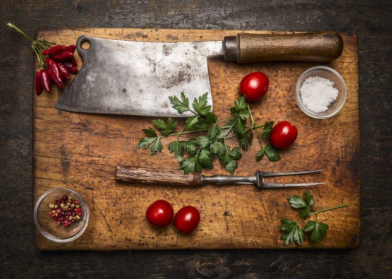 Slasher肉叉子肉胡椒盐蕃茄,在木切板顶视图的新鲜的草本在土气木背景 免版税库存照片