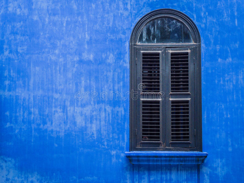 Slat window on blue wall stock image