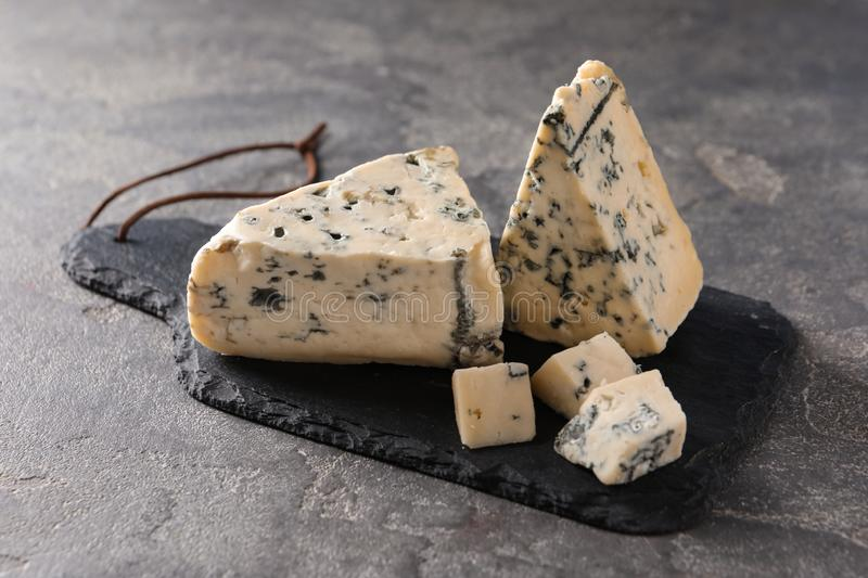 Slate board with delicious blue on stone surface. Slate board with delicious blue cheese on stone surface stock photo