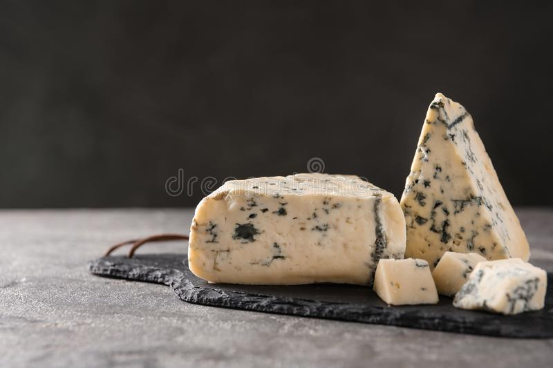 Slate board with delicious blue cheese on stone surface. Space for text royalty free stock photography
