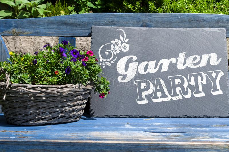 Slate chalkboard on blue wooden bank with plants with the german words for garden party. Gartenparty royalty free stock images