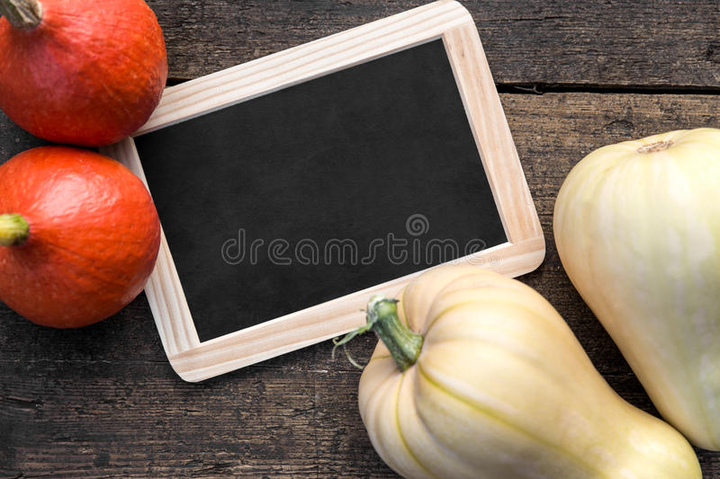 Slate with copyspace, Hokkaido and butternut pumpkins on wooden stock photography