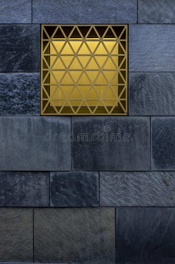 Slate facade with yellow luminous window with privacy screen and grid as burglary protection. At dusk royalty free stock photos