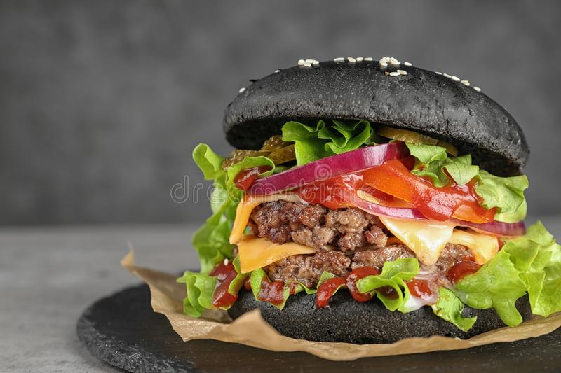 Slate plate with black burger on table, closeup. Space for text stock photography