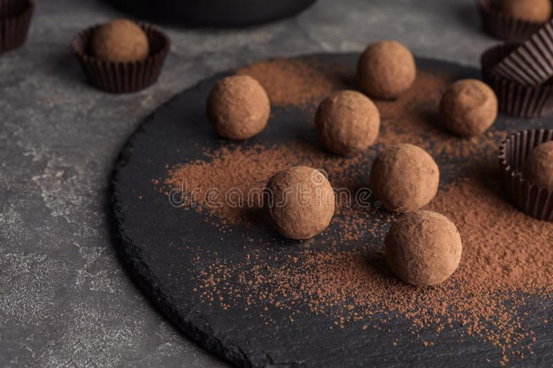 Slate plate with chocolate truffles on grey background. Space for text stock images