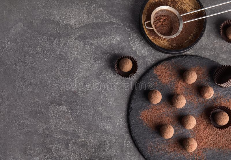 Slate plate with chocolate truffles on grey background, top view. Space for text stock image