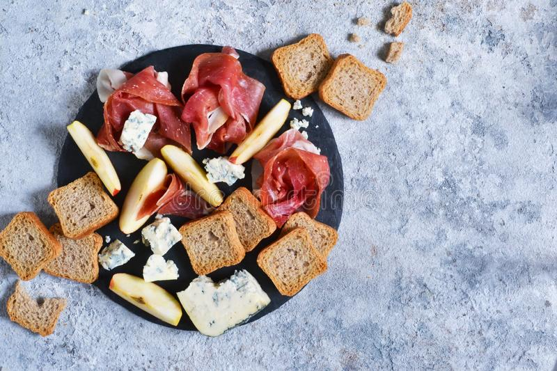 Slate plate with delicacies: jamon, blue cheese, brie. View from above. Slate plate with delicacies: jamon, blue cheese, brie stock photo