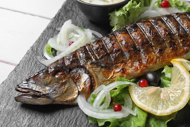 Slate plate with delicious grilled fish and sauce. On table, closeup royalty free stock images