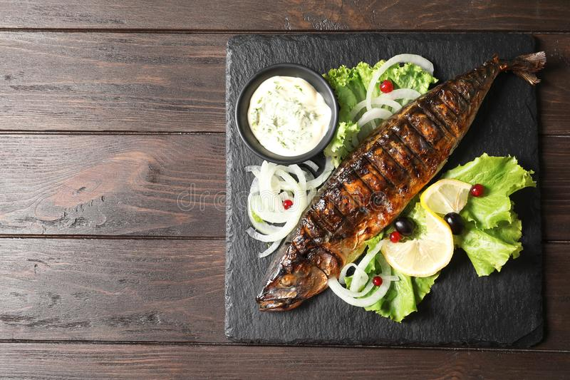 Slate plate with delicious grilled fish. And sauce on wooden table, top view royalty free stock photo