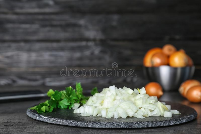 Slate plate with fresh chopped onion. On table royalty free stock photography