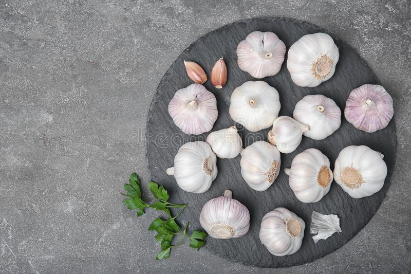Slate plate with fresh garlic on gray background. Top view royalty free stock image