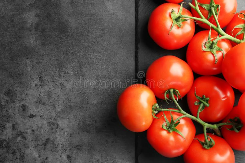 Slate plate with fresh ripe tomatoes. On grey background, top view stock image