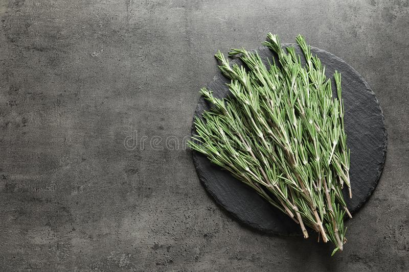 Slate plate with fresh rosemary twigs on tabl. E, top view stock photos