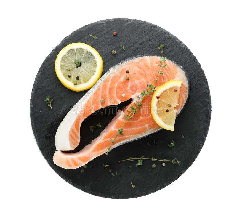 Slate plate with fresh salmon steak and lemon. On white background, top view stock photo