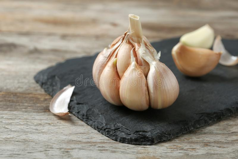 Slate plate with garlic. On wooden background stock photo