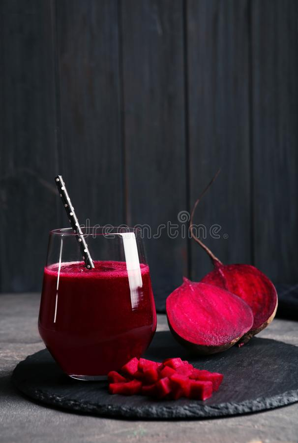 Slate plate with glass of beet smoothie on table royalty free stock photos