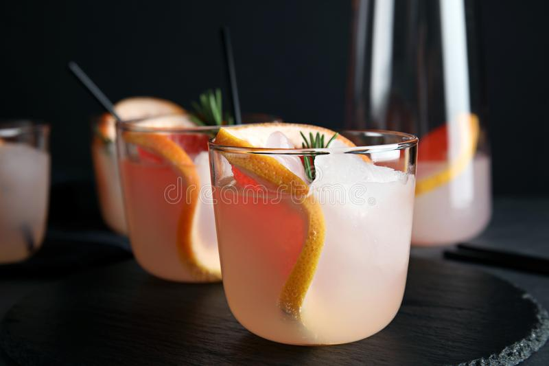 Slate plate with glasses of grapefruit cocktails on table. Closeup stock images