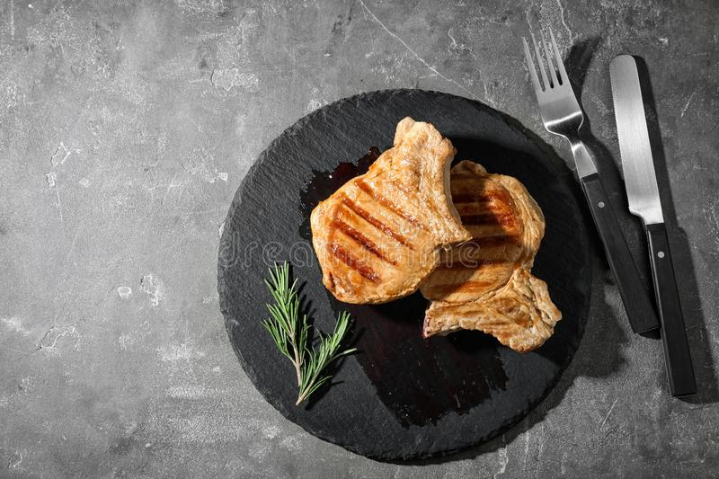 Slate plate with grilled meat on grey background, top view. Space for text stock photo