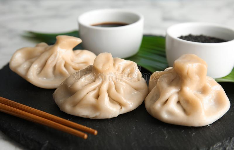 Slate plate with tasty baozi dumplings on table. Closeup royalty free stock photo