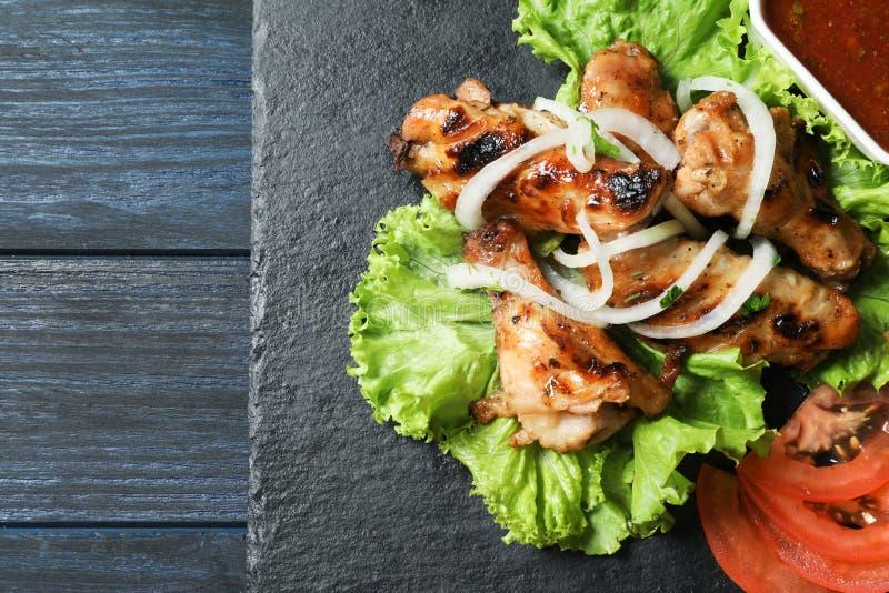 Slate plate with tasty shish kebab and sauc. E, top view stock image