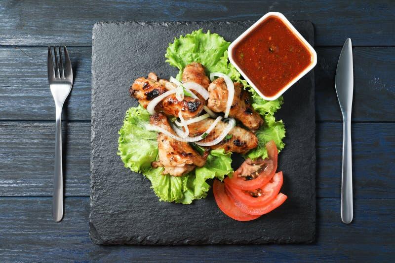Slate plate with tasty shish kebab. And sauce, top view stock image