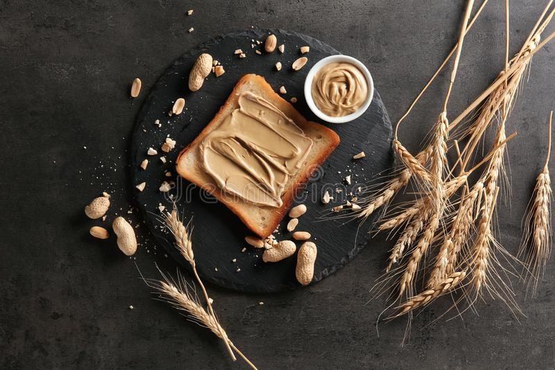 Slate plate with tasty toast and peanut butter on table stock photo