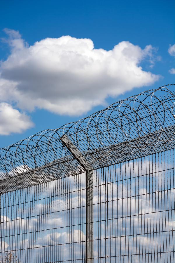 Slatted fence with barbed wire on top. Cloudy sky behind the fence. imprisonment concept royalty free stock image