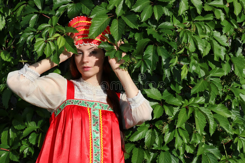 Slav in traditional dress ivy wall tree. Cute pretty girl in a traditional Slavic dress on nature in an unspoilt location royalty free stock photos