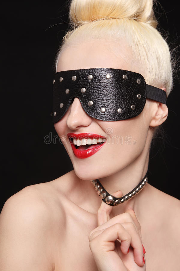 Slave. Portrait of young beautiful smiling woman in studded blindfold and collar royalty free stock photos
