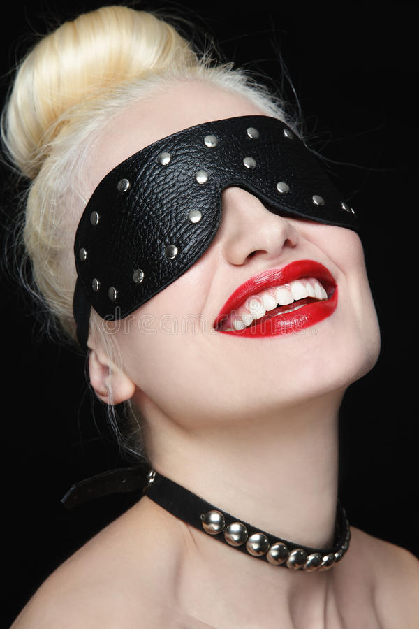 Slave. Portrait of young beautiful smiling woman in studded blindfold and collar royalty free stock image