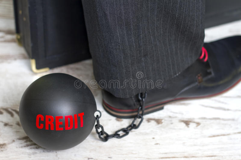 In slavery of credit concept with metal ball on chain and leg stock image