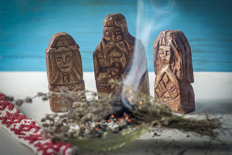 Slavic mystical ritual, CLEANING SPACE OF SMOKE OF MEDICINAL HERBS. In front of the idols of the Slavic gods, bunches of grass cre. Ate smoke. Selective focus stock photos