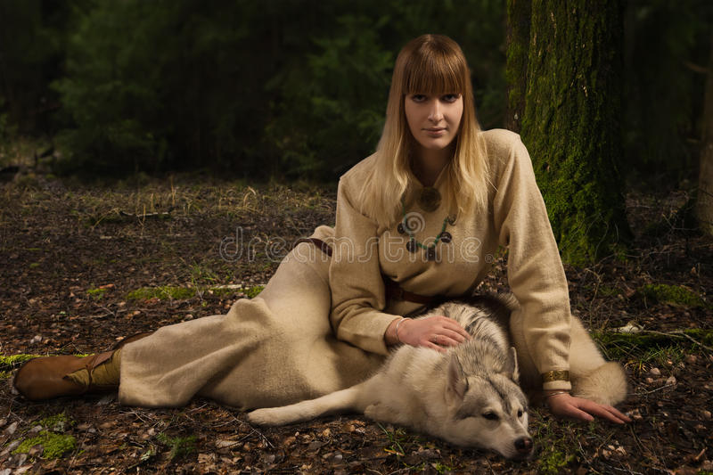 Slavonian girl and siberian husky in the deep forest royalty free stock photos