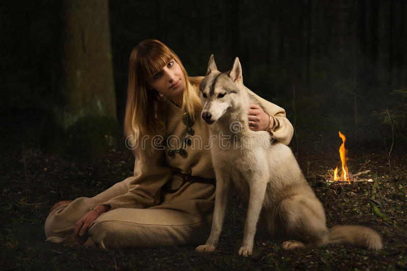 Slavonian girl and siberian husky in the deep forest royalty free stock photo