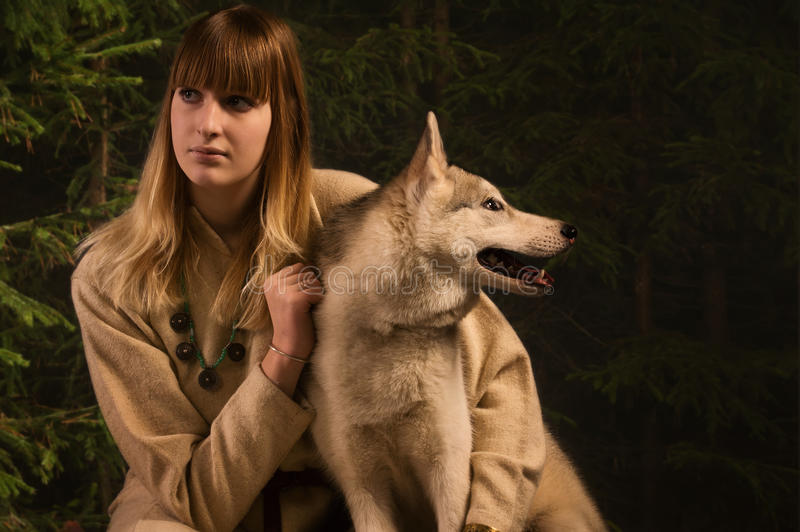 Slavonian girl and siberian husky in the deep forest royalty free stock image