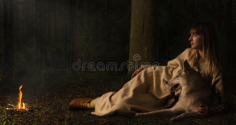 Slavonian girl and siberian husky in the deep forest stock photo