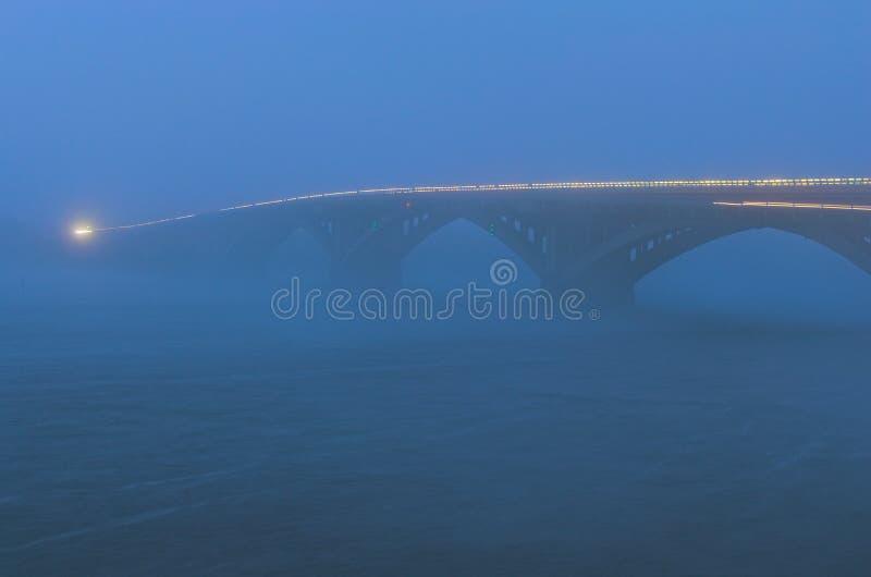 Slecht de herfstweer en gevaarlijk automobiel verkeer op de brug Lichte voertuigen in mist Het concept mistig weer in de stad royalty-vrije stock afbeeldingen