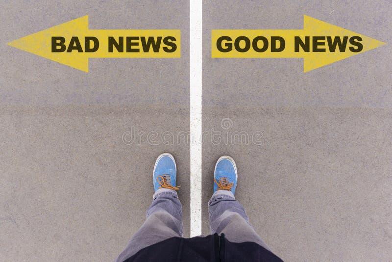 Slecht nieuws, de goede pijlen van de nieuwstekst op asfaltgrond, voeten en schoen royalty-vrije stock fotografie