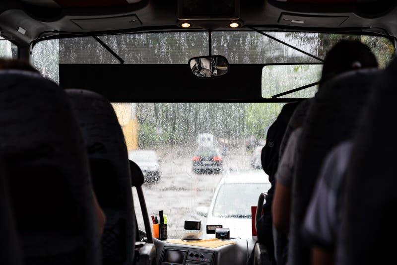 Slecht weer buiten, bus met passagiers, mening van binnenuit aan straat door het venster stock afbeeldingen