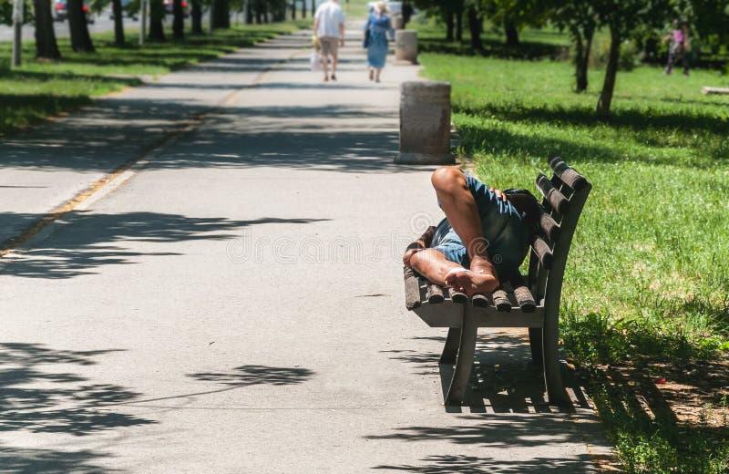 Slechte blootvoetse dakloze mens of vluchtelingsslaap op de houten bank op de stedelijke straat in de stad, sociaal documentair c royalty-vrije stock fotografie