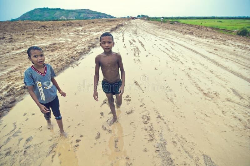 Slechte Cambodjaanse jonge geitjes die in modder spelen stock foto