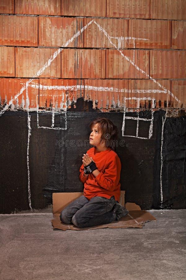 Slechte dakloze bedelaarsjongen die voor een schuilplaatsconcept bidden stock fotografie