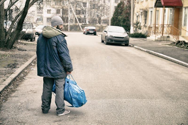 Slechte dakloze mens met zak op straat royalty-vrije stock fotografie