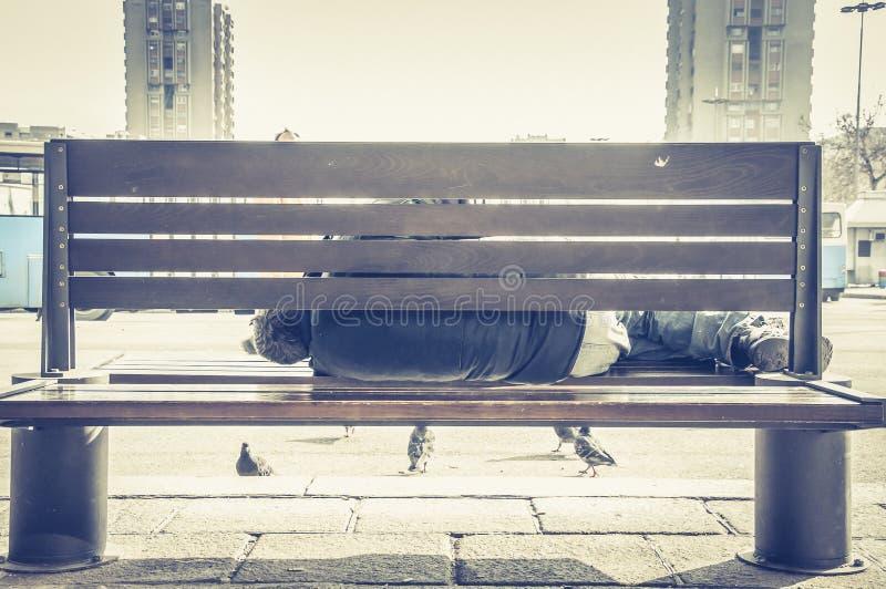 Slechte dakloze mens of vluchtelingsslaap op de houten bank op de stedelijke straat in de stad, sociaal documentair concept stock fotografie