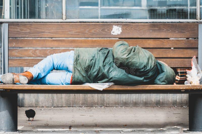 Slechte dakloze mens of vluchtelingsslaap op de houten bank op de stedelijke straat in de stad, sociaal documentair concept stock foto