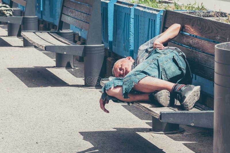 Slechte dakloze mens of vluchtelingsslaap op de houten bank op de stedelijke straat in de stad, sociaal documentair concept, sele royalty-vrije stock fotografie